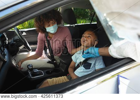 Medical worker wearing ppe suit taking swab tests of african american mother with son sitting in car. medical precautions, lifestyle during covid 19 pandemic.