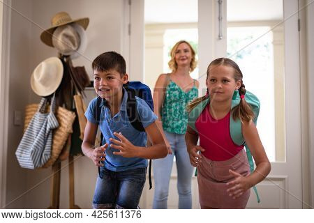 Happy caucasian mother with son and daughter at home back from school smiling. family quality time, leisure time concept.