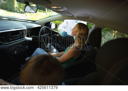 Medical worker wearing ppe suit taking swab tests of caucasian mother with son sitting in car. medical precautions, lifestyle during covid 19 pandemic.