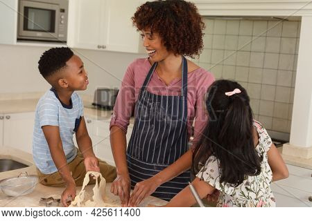 Happy african american mother with son and daughter baking in kitchen, cutting cookies. family enjoying quality free time together.