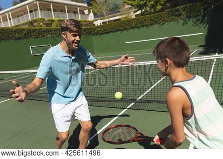 Happy caucasian father and son outdoors, playing tennis on tennis court. family enjoying healthy free time activities together.