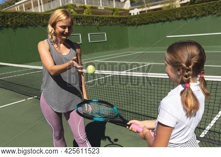 Happy caucasian mother with daughter outdoors, playing tennis on tennis court. family enjoying healthy free time activities together.