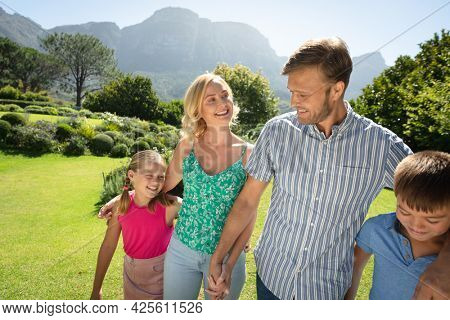 Happy caucasian couple with daughter and son outdoors, walking in sunny garden. family enjoying quality free time together.