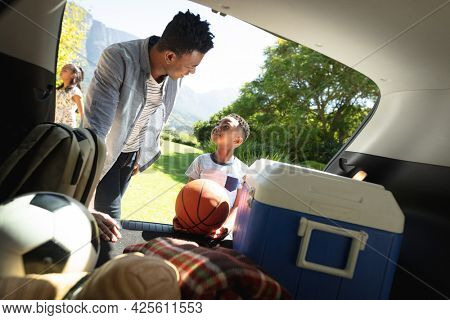 Happy african american father with son and daughter outdoors, preparing for picnic on sunny day. family enjoying quality free time together.