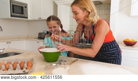 Caucasian mother and daughter baking and smiling in kitchen. family enjoying quality free time preparing food together.
