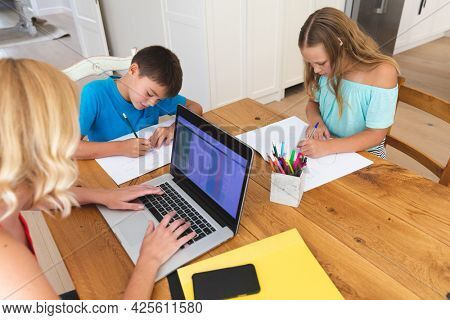 Caucasian mother using laptop and her daughter and son doing homework in kitchen. family domestic life, spending time working together at home.