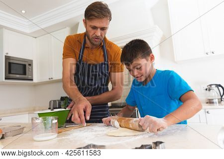 Caucasian father and son baking and smiling in kitchen. family enjoying quality free time preparing food together.