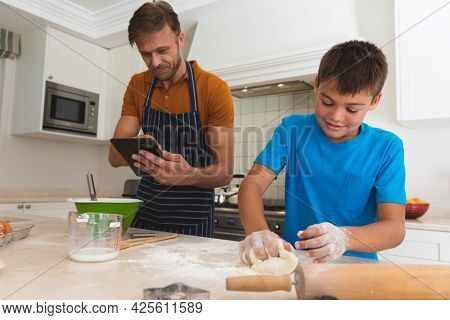 Caucasian father using tablet and son baking and smiling in kitchen. family enjoying quality free time preparing food together.