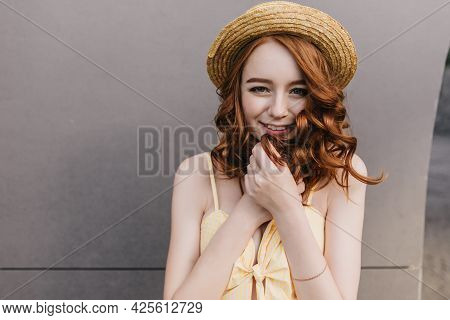 Playful White Girl In Hat Smiling On Gray Background And Looking To Camera. Portrait Of Good-humoure