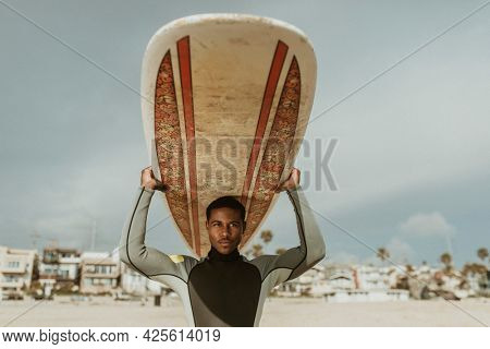 Surfer carrying a surfboard at the beach