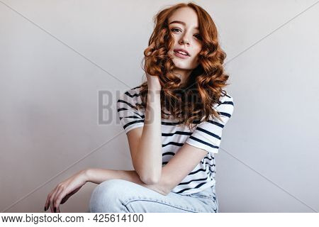 Interested Ginger Woman In Jeans Sitting In Studio And Looking To Camera. Indoor Photo Of Good-humou
