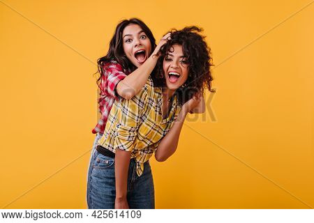 Crazy Emotional Girls Are Dabbling And Having Fun On Orange Background. Woman Laughs And Plays Hair