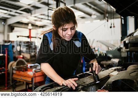 Female mechanic checking under the hood of a car