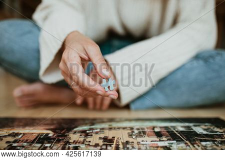 Woman putting together a jigsaw puzzle during self-quarantine