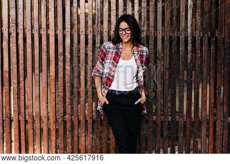Adorable Tanned Female Model Enjoying Spring Photoshoot. Good-humoured Caucasian Girl In Glasses Chi