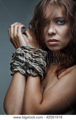redhaired woman bondage on gray background