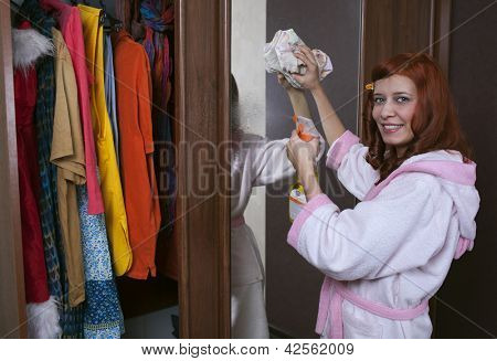 woman cleaning furniture cabinet with yellow duster
