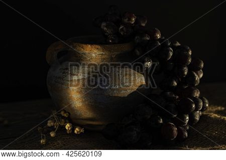 Dark Moody Food Still Life In A Rustic Style. Ripe Black Grapes Closeup.