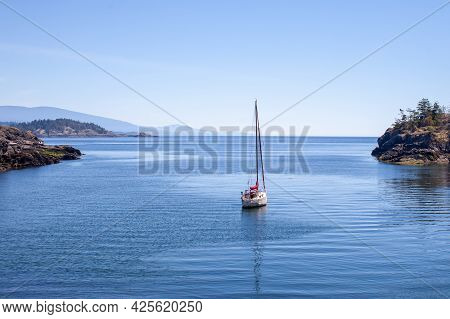 A Sailboat Is Anchored (moored) In A Small Cove On The Southern End Of Thormanby Island, On The Suns