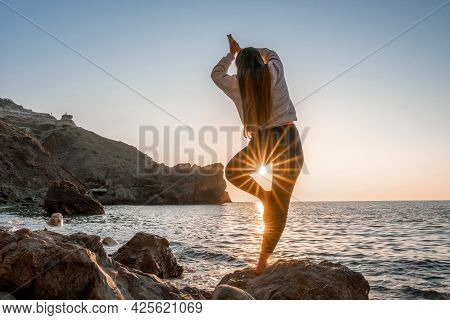 Young Woman With Long Hair In Sportswear And Boho Style Braclets Practicing Outdoors On Yoga Mat By