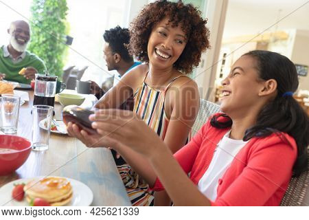 Happy african american multi generation family sitting at table laughing during breakfast. family enjoying quality free time together.