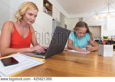 Caucasian mother using laptop and her daughter doing homework smiling at home. family domestic life, spending time learning together at home.