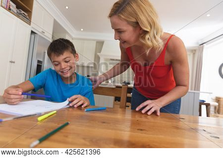 Caucasian mother doing homework with her son and smiling at home. family domestic life, spending time learning together at home.