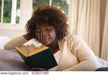 Happy african american woman relaxing in bedroom, lying on bed reading book and smiling. domestic lifestyle, enjoying leisure time at home.