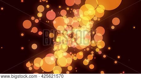 Orange and yellow glowing translucent circles effervescing on a dark background. light, colour, energy and movement concept, digitally generated image.