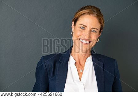 Close up face of confident mature businesswoman in formal clothing with copy space. Positive successful business woman looking at camera on gray wall. Beautiful middle aged woman standing on grey wall