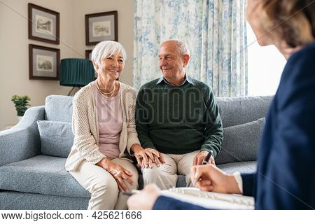 Medical advisor during home visit with senior couple. Financial insurance agent in conversation with old couple. Business agent planning with a retired couple their future investment opportunities.