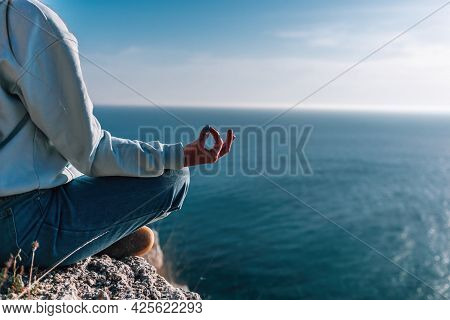 A Young Tourist Woman Enjoying Sunset Over Sea Mountain Landscape While Sitting Outdoor. Womens Yoga