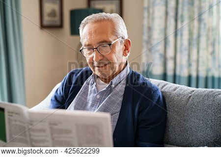 Senior man wearing spectacles reading a newspaper while relaxing at home. Retired man sitting on couch reading newspaper for daily updates. Old man in glasses relaxing at home.