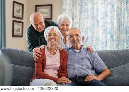 Portrait of happy elderly people on couch at care centre looking at camera. Senior couple posing for a photo sitting on couch in nursing home. Cheerful old man and beautiful woman looking at camera.