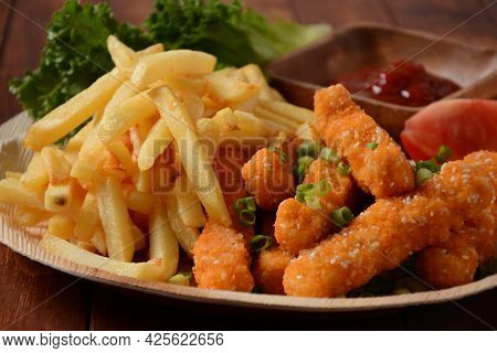 Chicken Breast Nuggets With Popular Sauce And Chips And Vegetables For Choice On Wooden Background