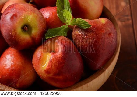 Nectarine. Ripe Juicy Organic Nectarines  In A Wooden Bowl. Whole And Sliced Fruit On A Wooden Table