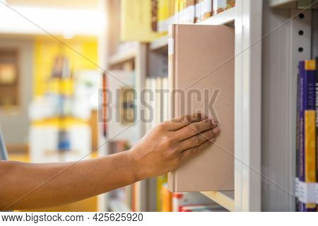 Book And Library, Close Up Hand Choosing And Picking Books From Bookshelf In Library. Concepts Of Re