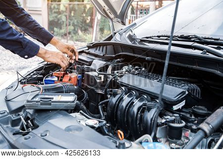 Technician Auto Mechanic Using A Power Meter To Check The Car Batter Electric Or Electrical And Engi