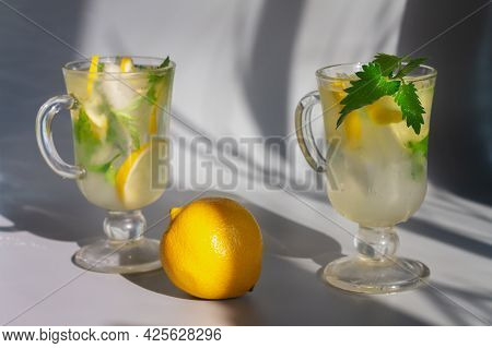 A Transparent Glass With A Cold Mojito Drink With Ice, Lemon, Mint, Lemon Balm Leaves For Refreshing