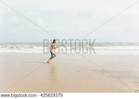 A Caucasian Woman Runner In Sportswear Outdoor Jogging At The Beach. Young Fitness Sport Female Runn