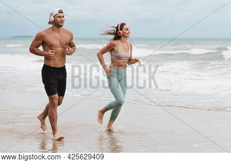 A Caucasian Man And Woman Runner In Sportswear Outdoor Jogging At The Beach. Young Fitness Sport Cou