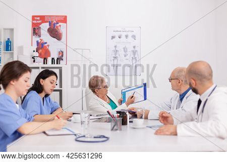 Physiotherapist Doctor Explaining Sickness Diagnosis Using Clipboard Presenting Medical Expertise Wh