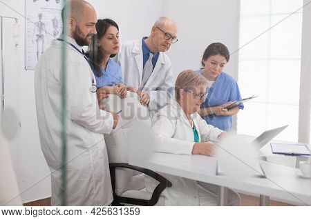 Specialists Physicians Teamwork Looking At Laptop Computer Examining Disease Tomography Discussing H