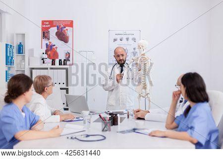 Physician Doctor With Stethoscope Holding Hand Bone Explaining Body Human Skeleton Presenting Anatom