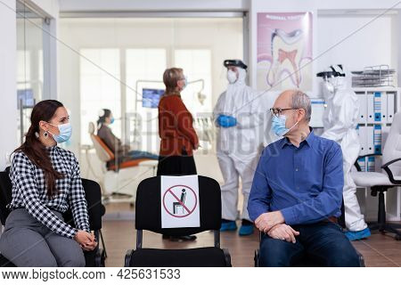 Senior Man With Face Mask Discussing With Woman Patient In Stomatology Clinic In Waiting Room, Keepi