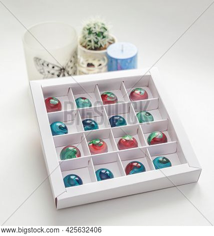 Tempered Chocolate Candies With Glossy Painted Body In A Box With Blurred Background And Bokeh Eleme