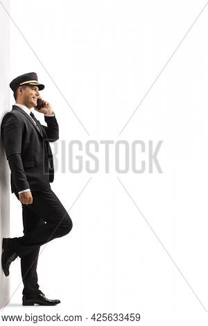 Full length profile shot of a chauffeur leaning on a wall and talking on a mobile phone isolated on white background