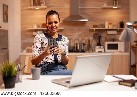 Freelancer Woman Having A Conversation On Phone While Working From Home Late At Night. Employee Usin