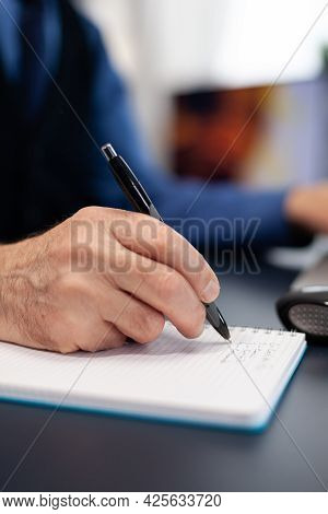 Close Up Of Man Taking Notes On Notebook While Working From Home. Elderly Man Entrepreneur In Home W
