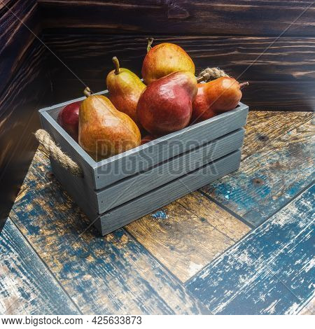 A Blue Wooden Box With Rope Handles Is Filled With Ripe Pears. Red Fruits With A Shiny Skin. Backgro